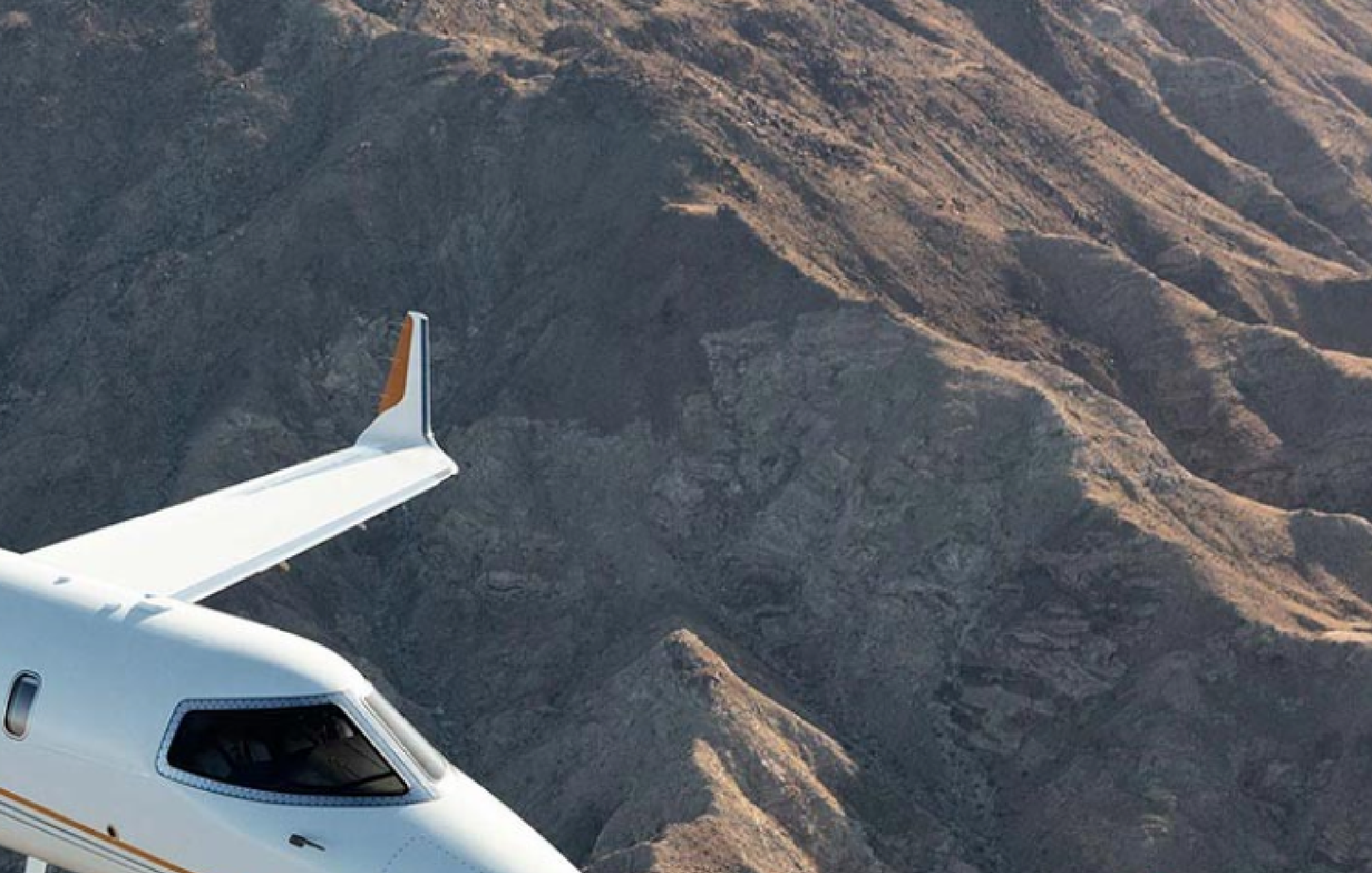 Jet flying next to mountains